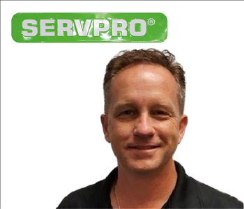 Bill Shook for SERVPRO on wall - male employee in black shirt