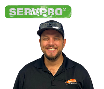 Male employee Zach Mauser PM- wearing SERVPRO uniform standing in front of white wall